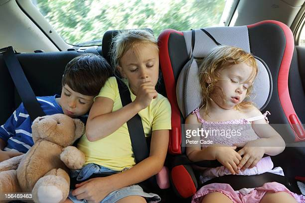 Three children asleep in the back of car