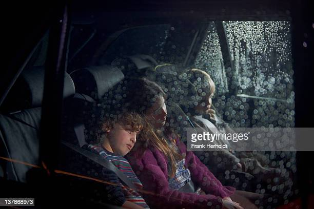 Three children asleep in the rear seat of a car