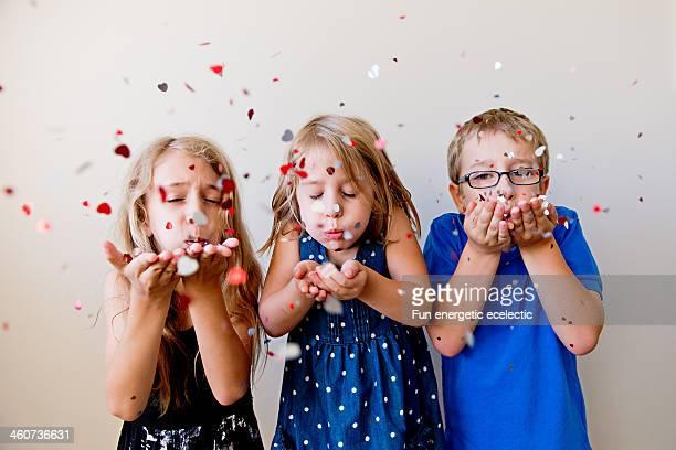 three children blowing confetti at camera