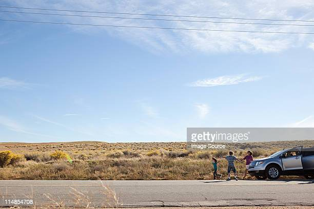 Three children by parked car in desert