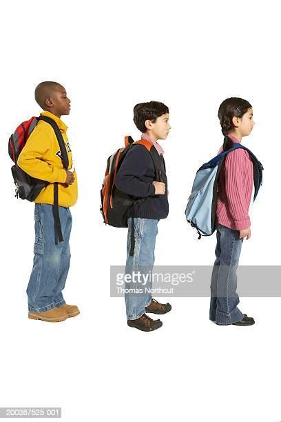 three children (7-9) carrying backpacks and shoulder bag, side view - somente crianças imagens e fotografias de stock