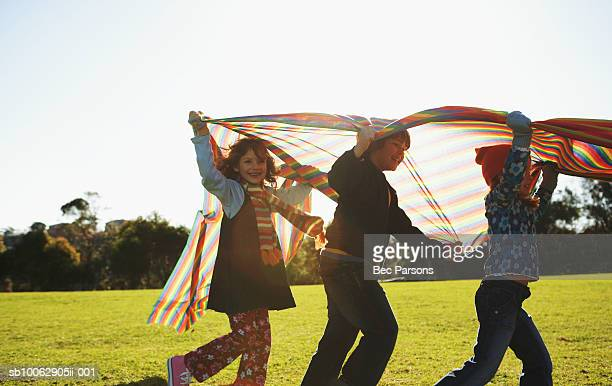 Three children (7-10) carrying piece of cloth in park