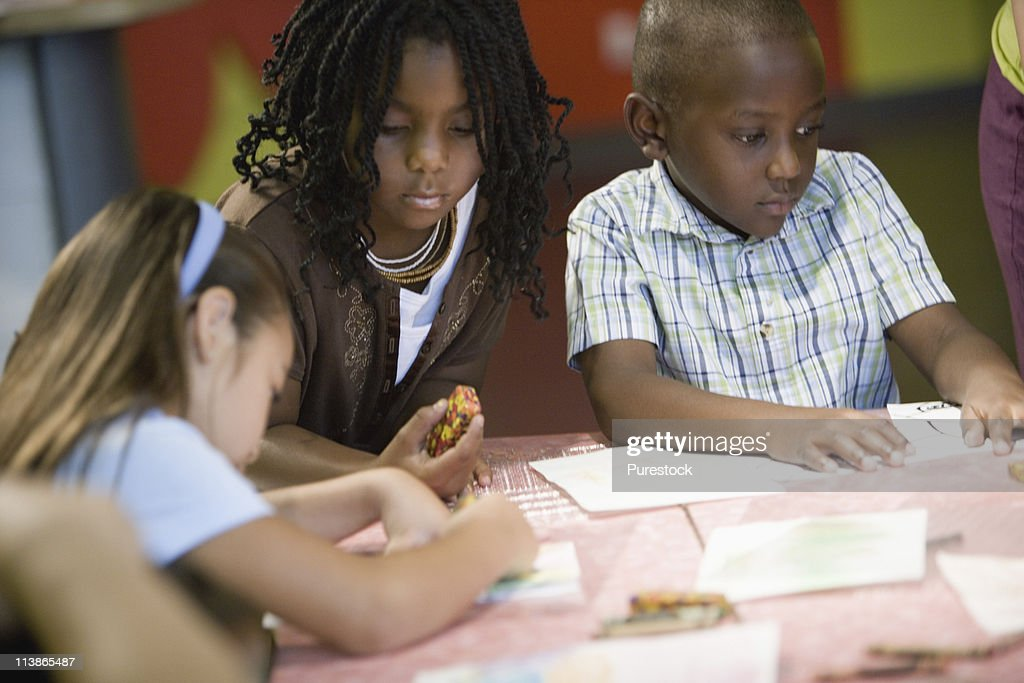 Three Children Coloring With Crayons Stock Photo