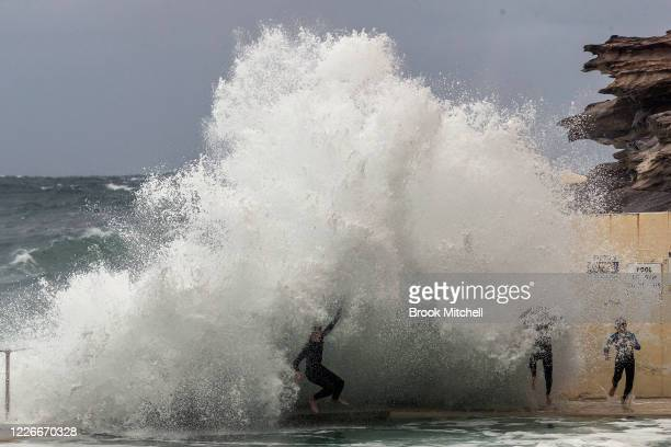 Three children do their best to avoid large waves crashing into the Bronte ocean pool on May 24 2020 in Sydney Australia Winter weather including...