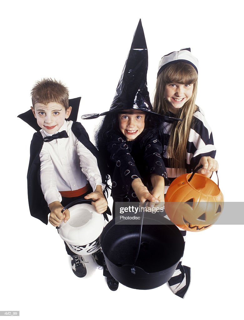 three children dressed for Halloween huddle together holding out candy pails : Stock Photo