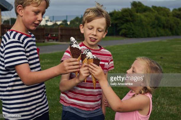three children enjoying eating ice cream - southport england stock pictures, royalty-free photos & images