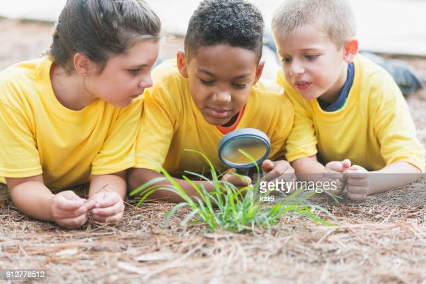 Three children exploring nature with magnifying glass