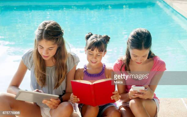 Three children girls reading and using trheir gadgets by a pool