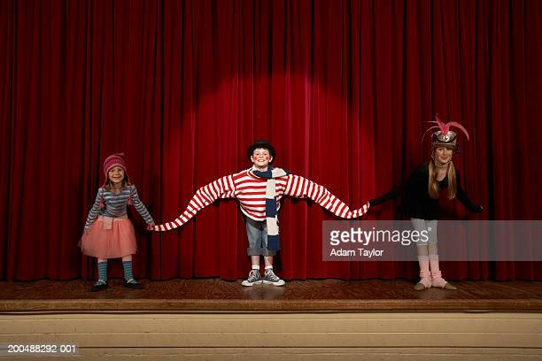 Three children (6-10) holding hands on stage, taking bow