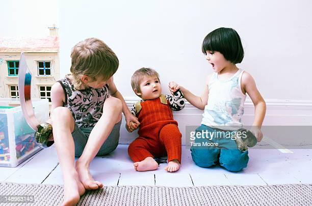 three children holding hands with toys