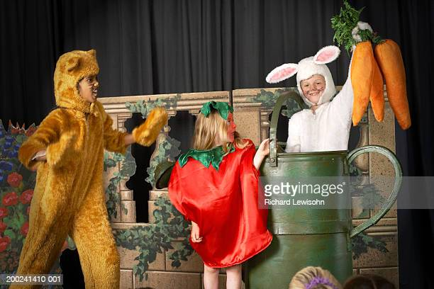 three children (5-9) in food and animal costumes performing on stage - school play stock photos and pictures