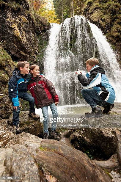 Three Children In Front Of A Waterfall, Bavaria, Germany, Europe