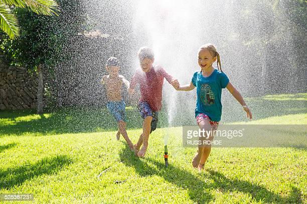 three children in garden running through water sprinkler - wet t shirt girls stock photos and pictures