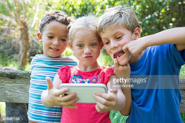 Three children in garden taking selfie on smartphone