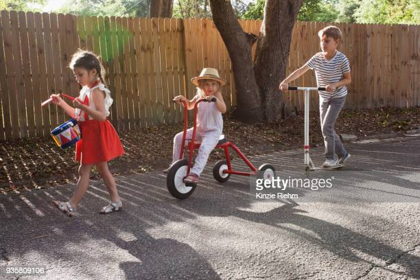 Three children in mini parade, banging drum, riding tricycle and using scooter