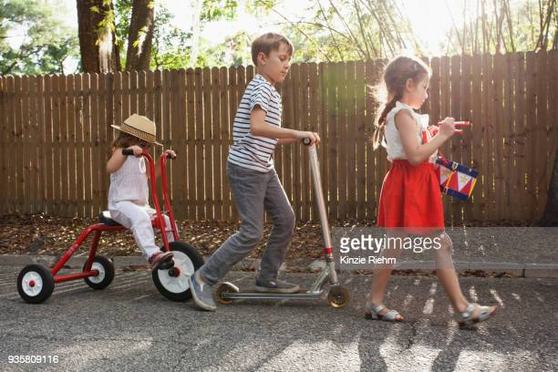 three children in mini parade, banging drum, riding tricycle and using scooter - parade stock pictures, royalty-free photos & images