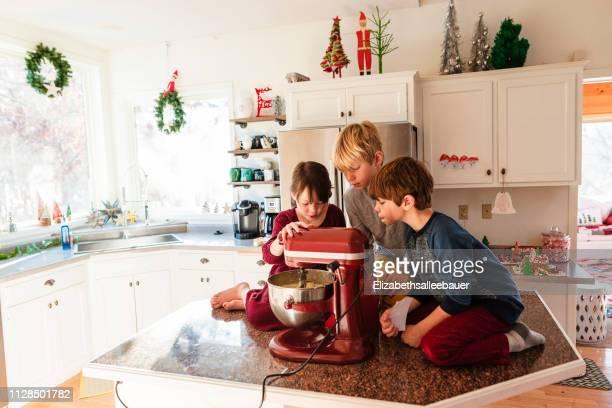 three children in the kitchen making a cake - 8 9 anni foto e immagini stock