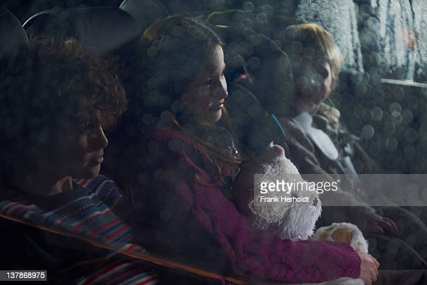 Three children in the rear seat of a car
