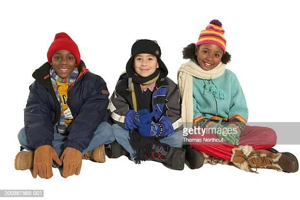 three children (8-10) in winter clothing sitting side by side, smiling - anorak abrigo de invierno fotografías e imágenes de stock