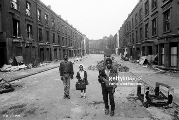 Three children, including a little girl carrying a satchel, walking along a street of slum housing in the notorious Gorbals district of Glasgow in...