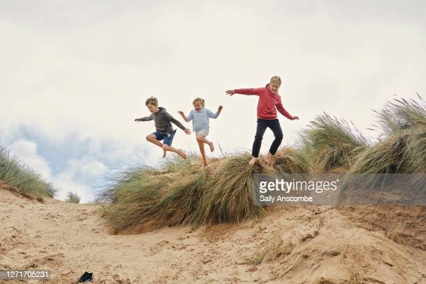 three children jumping of the sand dunes together - season 3 stock pictures, royalty-free photos & images