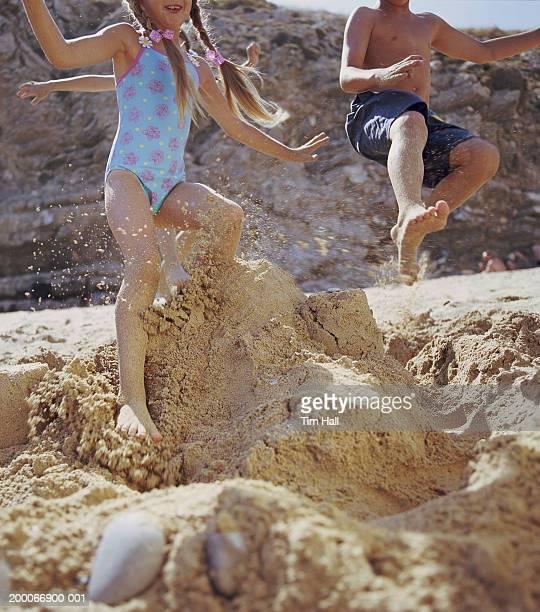 Three children (6-9) jumping on sandcastle on beach