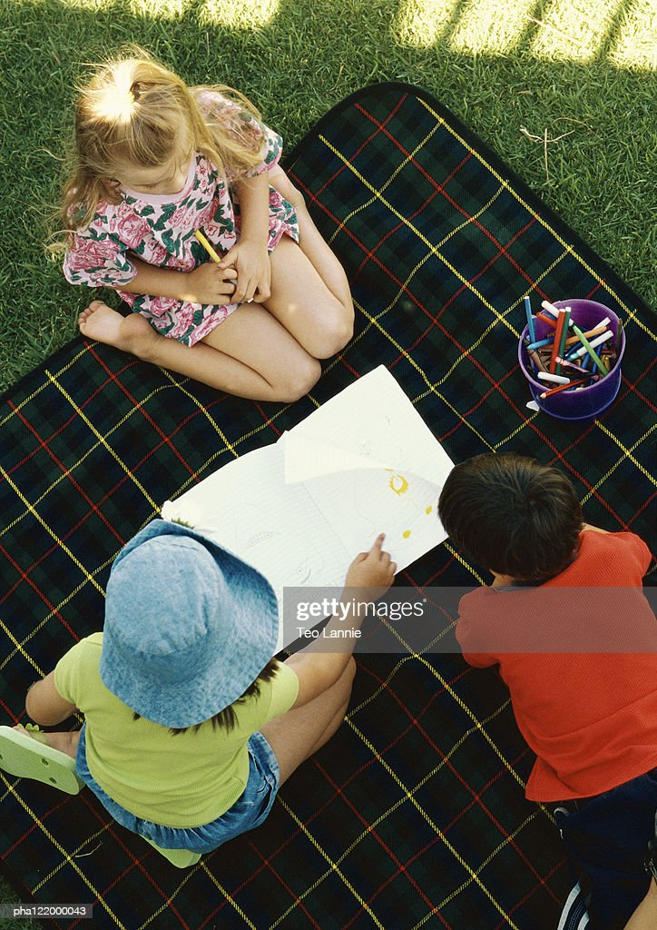 Three children kneeling on blanket outside, elevated view : Stockfoto
