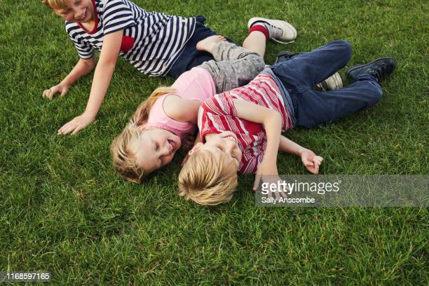 three children laughing together - southport england stock pictures, royalty-free photos & images