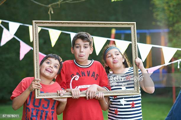 Three children looking through picture frame, sticking out tongues