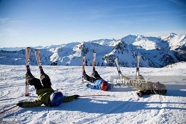 Three children lying in the snow.