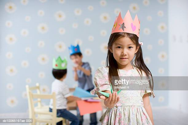 Three children (4-5) making origami in room, focus on girl in foreground