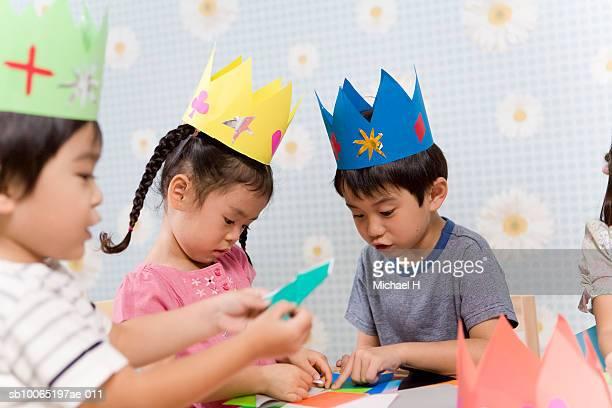 Three children (4-5) making origami in room (differential focus)