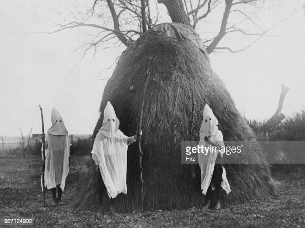 Three children mimicking the regalia and activities of the Ku Klux Klan, East Lots, Canarsie, Brooklyn, New York City, circa 1925. Calling themselves...