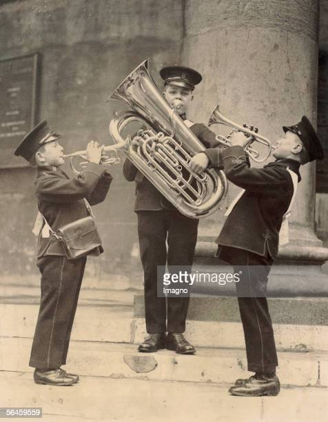 Three children of a school band in their uniforms with a tuba two cornets practising in front of the Queen's Hall in London for a competition of...