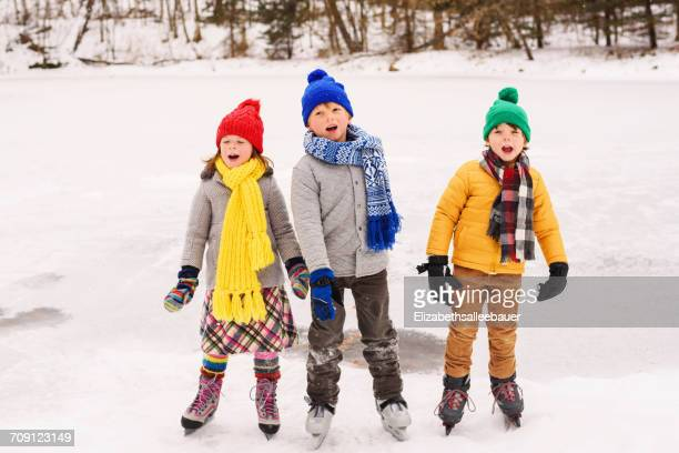 Three children on ice skates singing carols