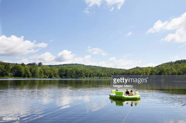 Three children on inflatable boat on lake