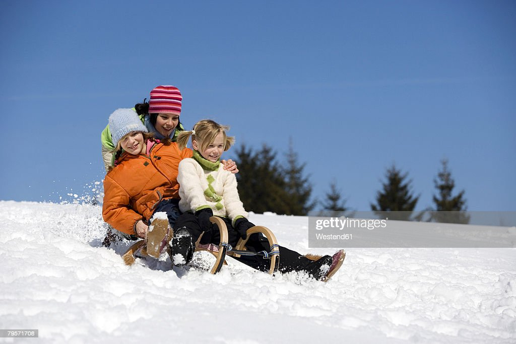 Three children on sledge : ストックフォト