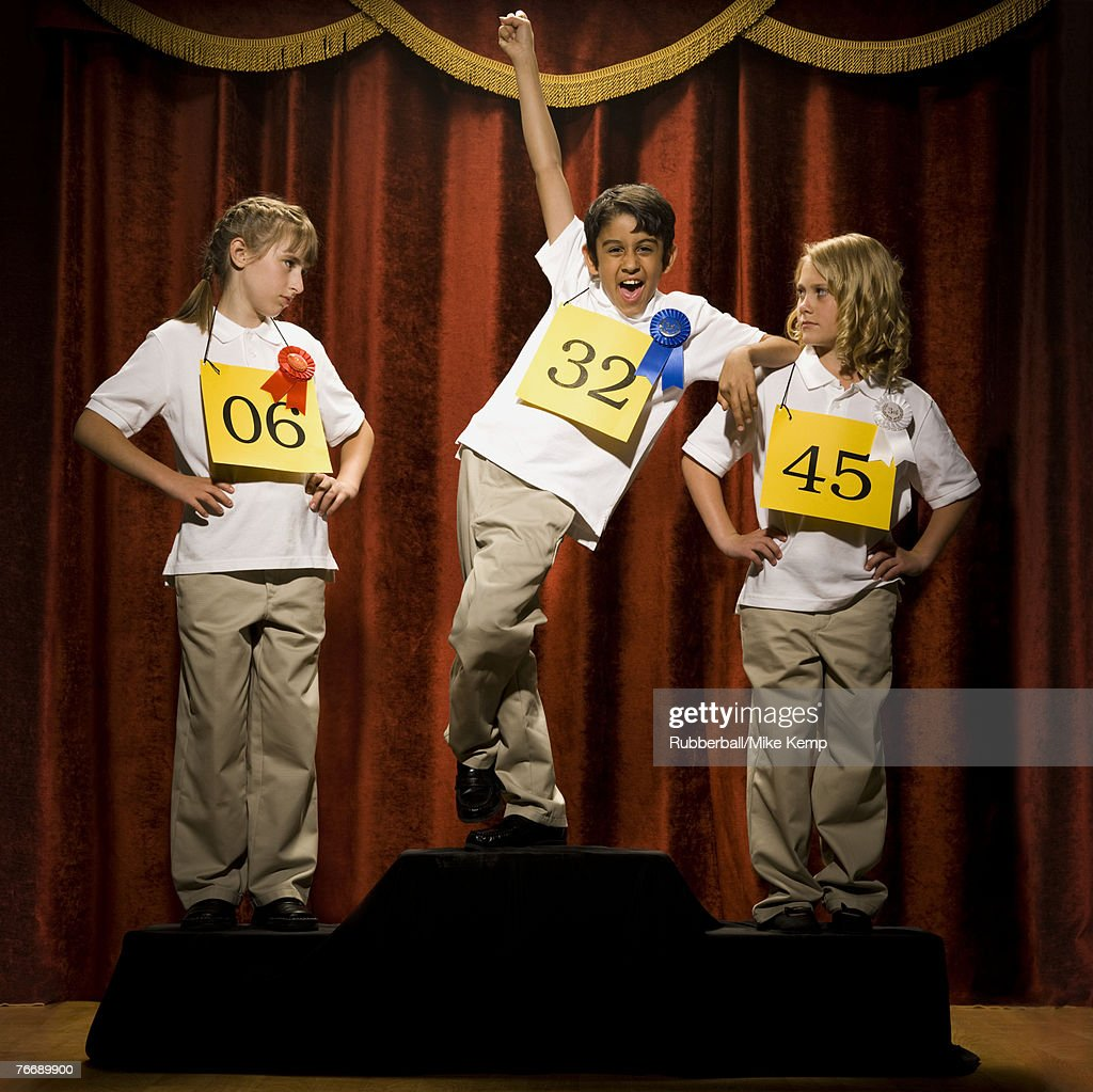 Three children on stage at winner's podium with ribbons smiling : Stock Photo
