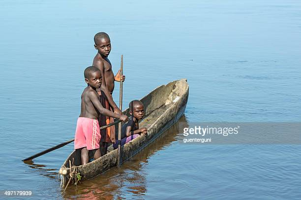 three children paddling in a pirogue on congo river - democratic republic of the congo stock photos and pictures