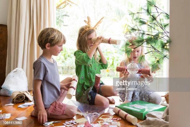 Three children peek inside Christmas crackers