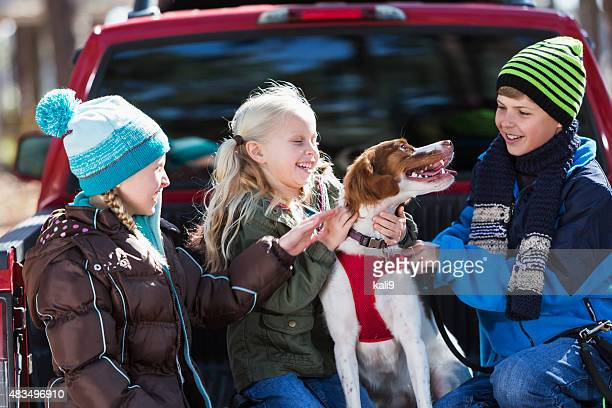 three children petting the family dog - brittany spaniel stock pictures, royalty-free photos & images