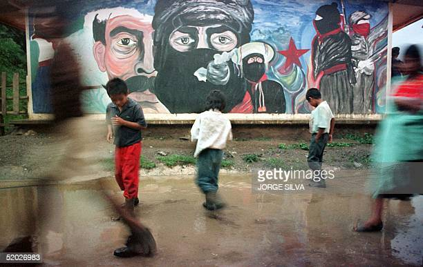Three children play in a puddle of water before a giant mural depicting Zapatista rebel leader Subcommandante Marcos smoking his trademark pipe...