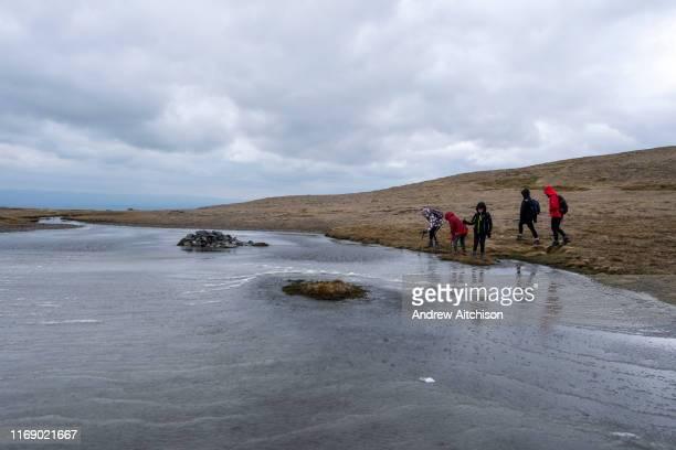 Three children play poking sticks into the frozen glacial lake below Doddick Fell near the summit of Blencathra Mountain Lake District Cumbria UK The...