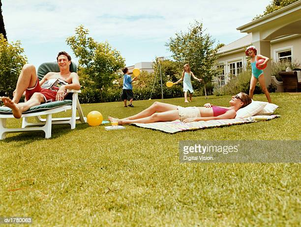Three Children Play With Balls in a Garden While Their Parents are Sunbathing