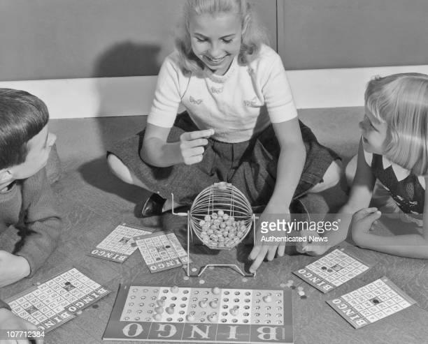 Three children playing a game of bingo circa 1960's