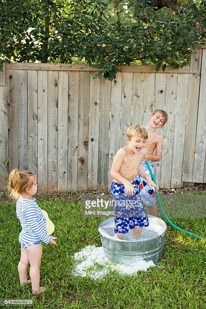 three children playing in a garden with a water-filled tub and hose. - たらい ストックフォトと画像