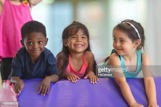 Three children playing in an indoor gym