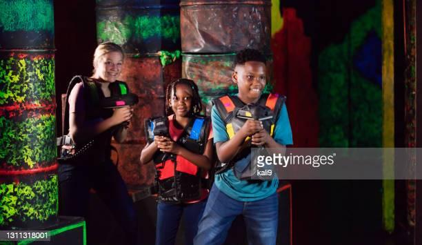 レーザータグを再生する3人の子供 - 鬼ごっこ ストックフォトと画像