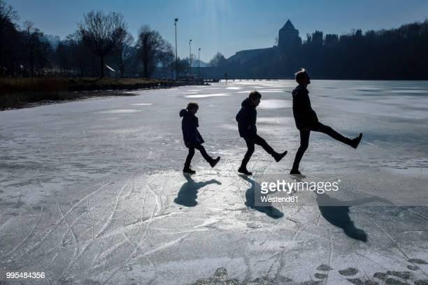 three children playing on icy surface - anpassen stock-fotos und bilder