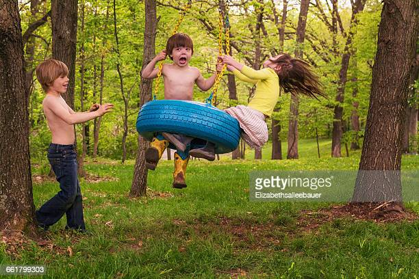 Three children playing on tyre swing in forest